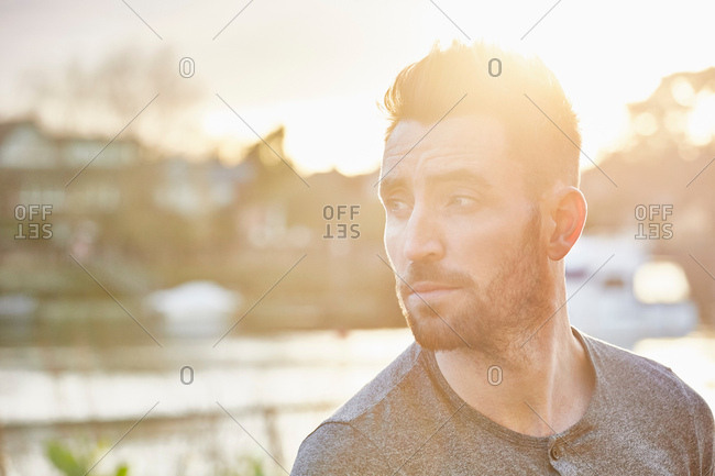 Hazy lens flare shot of bearded young man looking over his shoulder on riverside