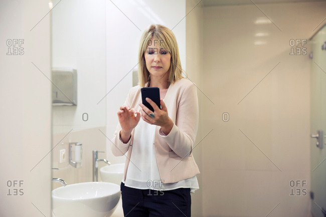 Woman using smartphone in bathroom