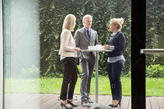 Colleagues standing at patio table enjoying refreshments