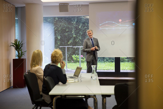 Colleagues in conference room, presentation on projection screen