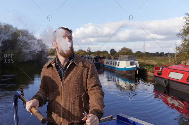 Man smoking e-cigarette on canal boat