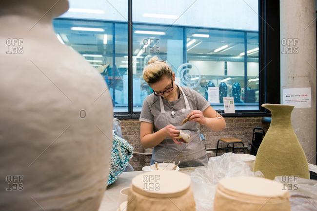 Woman in art studio glazing pottery