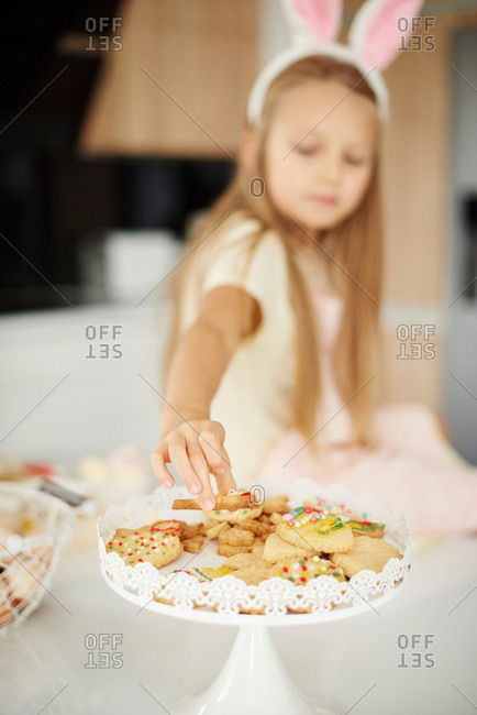 Girl selecting from easter biscuits on kitchen counter