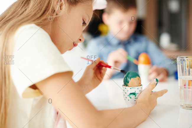 Girl painting hard boiled easter egg green at table