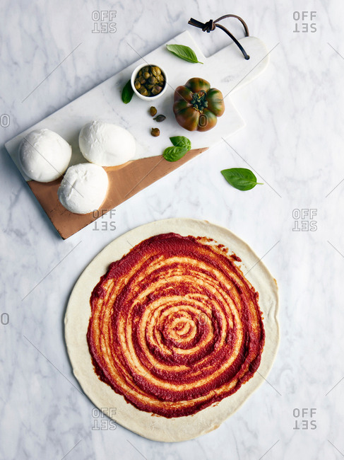 Pizza base with pizza ingredients on wooden board, overhead view