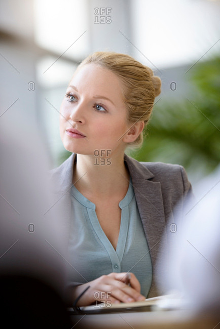 Portrait of businesswoman in meeting, differential focus