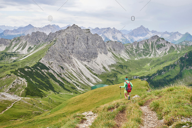 Rear view of female hiker hiking down valley in Tannheim mountains, Tyrol, Austria