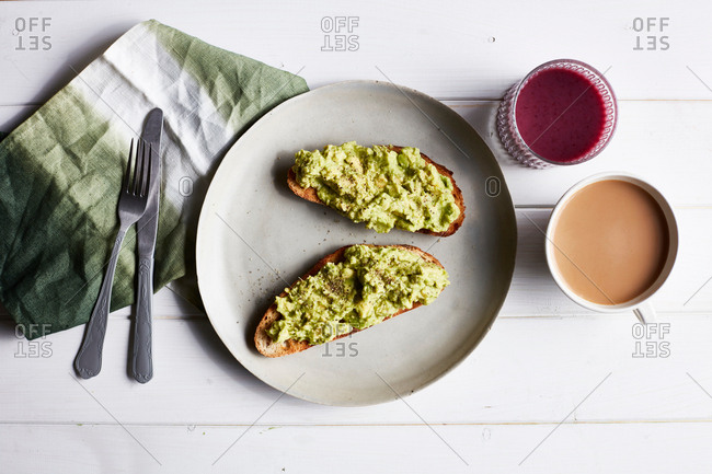 Avocado on toast on white plate, overhead view