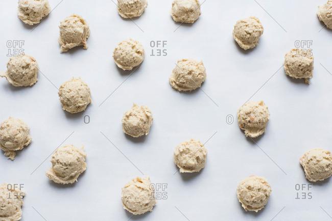 Balls of raw cookie dough on baking sheet, close-up
