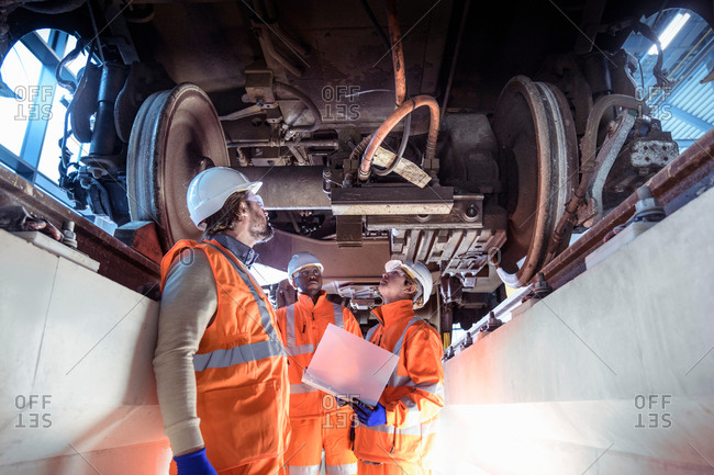 Instructor and apprentices under train in railway engineering facility