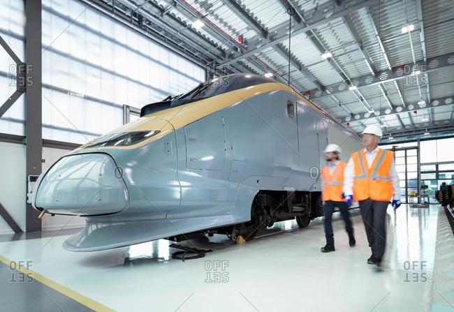 Engineers inspecting locomotive in railway engineering facility