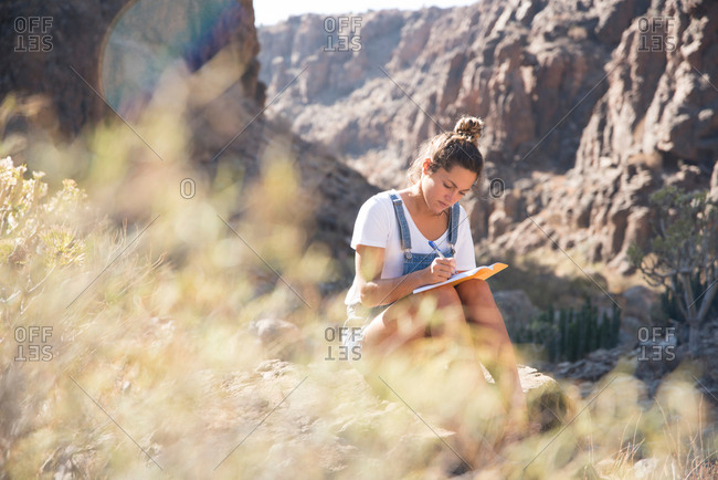 Young female hiker writing notes in valley, Las Palmas, Canary Islands, Spain