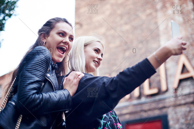 Two young women taking smartphone selfie on city street