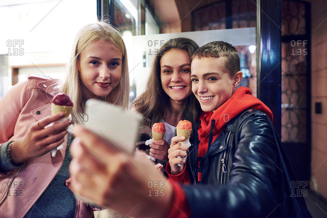 Three young women with ice cream cones taking smartphone selfie on city street