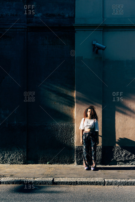 Woman standing in shadows by building, Milan, Italy