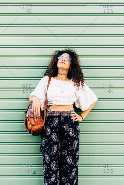 Woman posing against roller shutters
