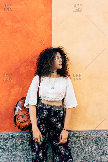Woman posing against dual-coloured wall, Milan, Italy