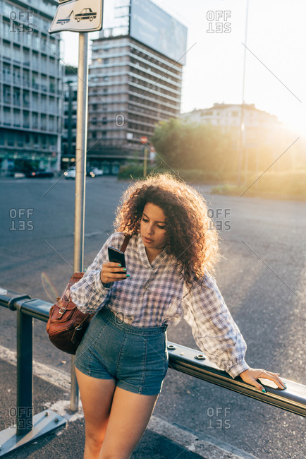 Woman using cellphone against street railing, Milan, Italy