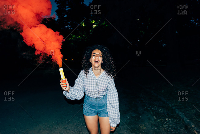 Woman holding flare in park at night