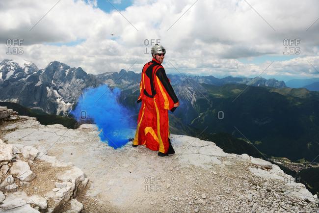 Base jumper on Dolomite mountains wearing wingsuit emitting blue smoke, Canazei, Trentino Alto Adige, Italy, Europe
