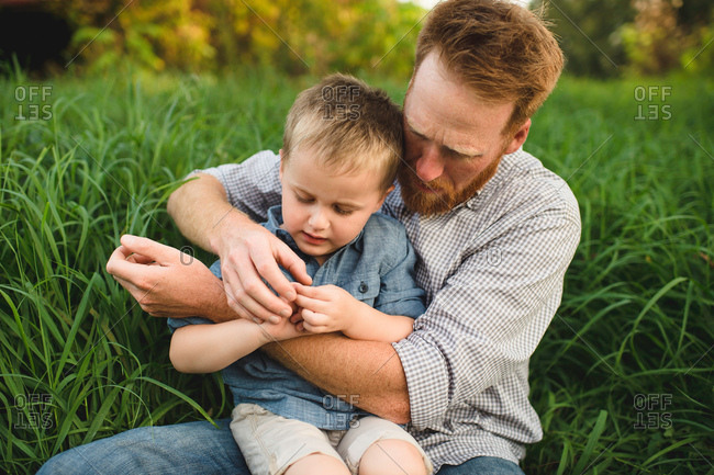 Father and son sitting in tall grass investigating nature