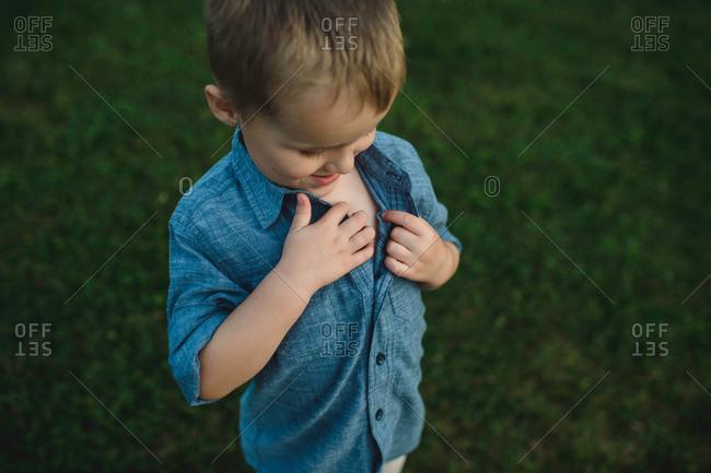 Boy unbuttoning shirt to investigate chest
