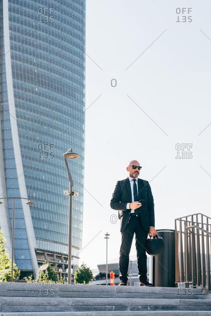 Portrait of mature businessman outdoors, holding motorcycle helmet