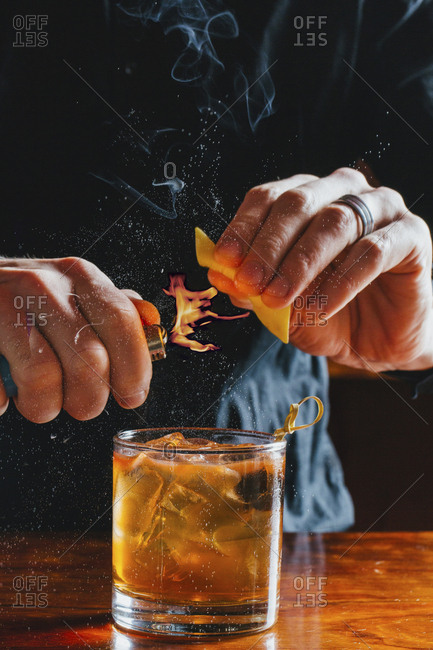 Midsection of bartender heating peel while preparing drink at bar counter