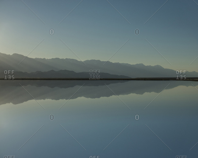 Symmetry view of Mono Lake by mountains against clear sky during sunset