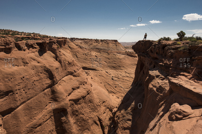 Mid distance view of man standing on cliff at Grand Staircase-Escalante National Monument against sky