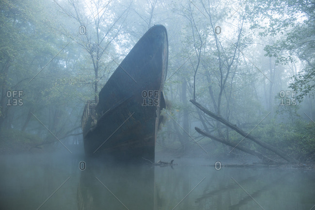 Abandoned boat on river in forest during foggy weather