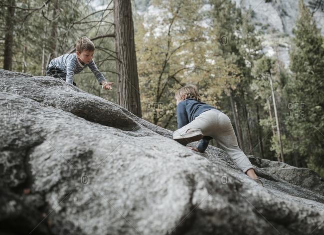 Brothers playing on rocks at Yosemite National Park
