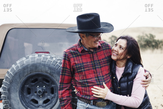 Cheerful couple looking each other while standing against vehicle on field