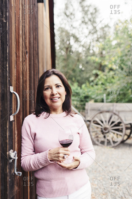 Portrait of confident mature woman with red wine standing by barn