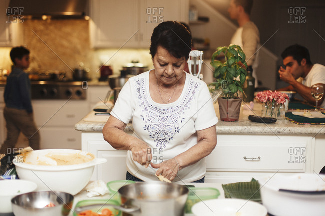 Senior woman cooking food while sons and grandson in background at kitchen
