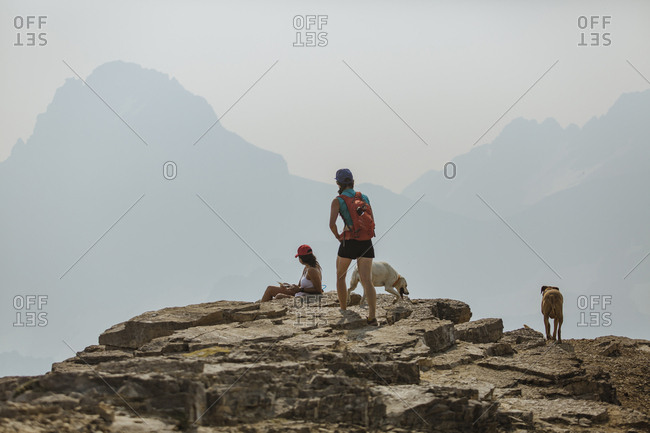 Female hikers with dogs on mountain against sky