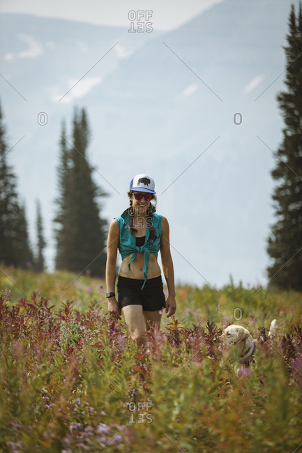 Woman with dog walking on field