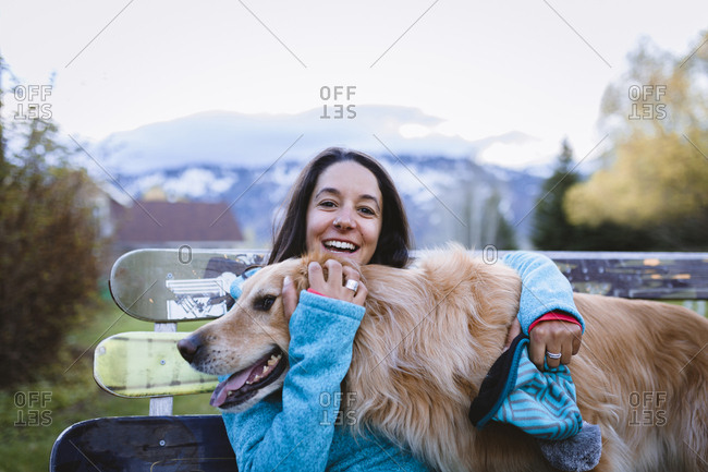 Portrait of cheerful woman with dog sitting on park bench