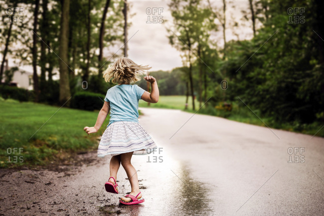 Rear view of girl dancing on wet road during monsoon