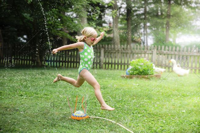 Side view of girl in swimwear running over sprinklers at yard
