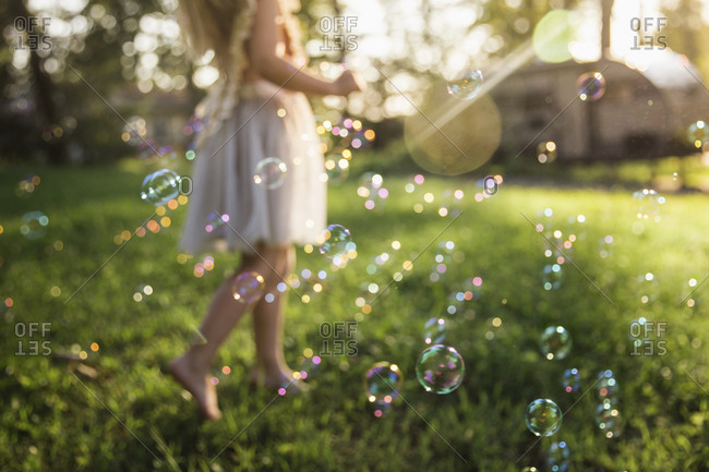 Low section of girl playing with bubbles on grassy field at park