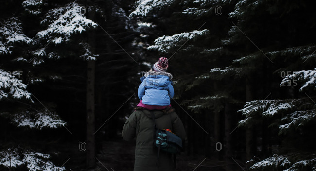 Rear view of father carrying daughter on shoulders while walking in forest during winter