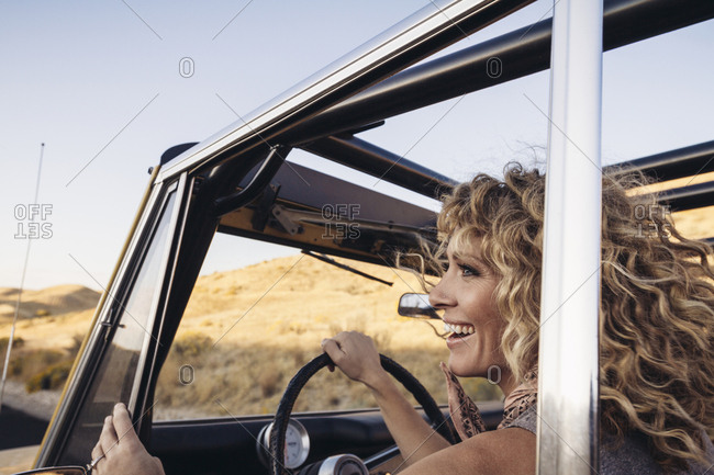 Cheerful woman looking away while sitting in off-road vehicle