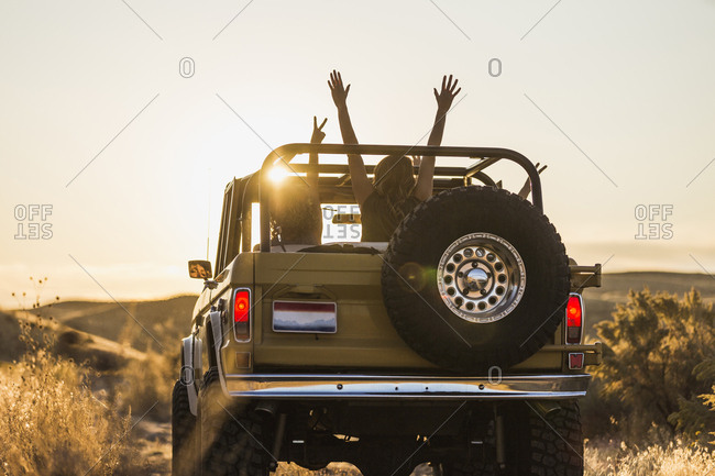 Rear view of female friends gesturing while traveling in off-road vehicle against sky