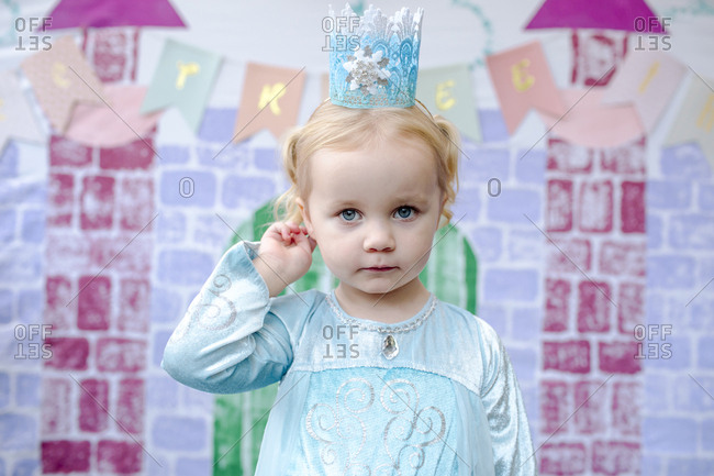 Portrait of cute girl standing against castle painting during princess party
