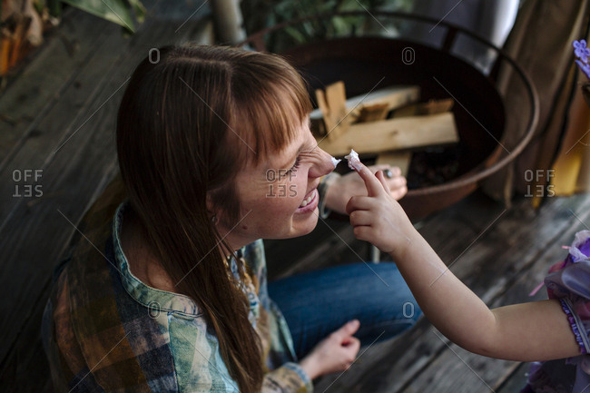 High angle view of girl applying cream on mother's nose during princess party