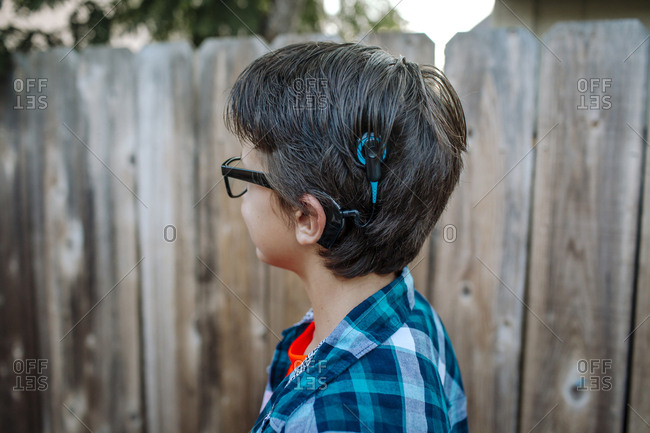 Side view of boy with hearing air standing against wooden fence at yard