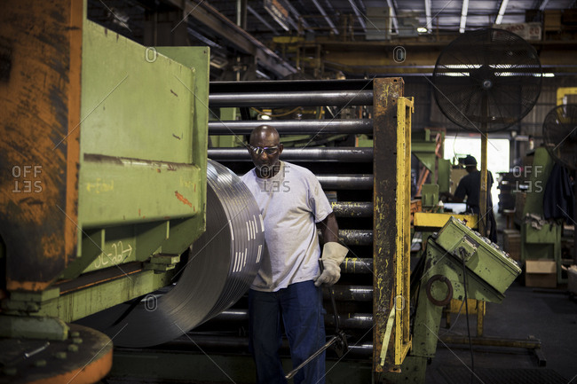 Manual worker working at machinery in metal industry