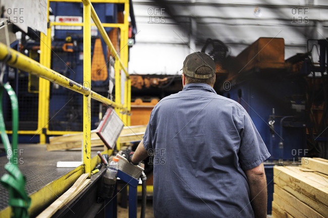 Rear view of worker standing by machine in metal Steel Industry Factory