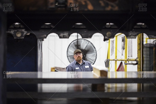 Portrait of worker standing against metal sheets in Steel Industry Factory
